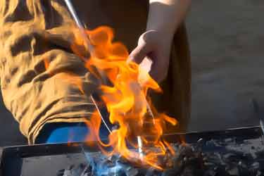 forging hot steel over fire