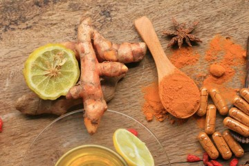 turmeric root next to powder and supplements