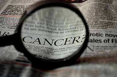 cancer headline in newspaper with magnifying glass