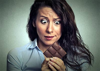 woman holding chocolate trying to resist