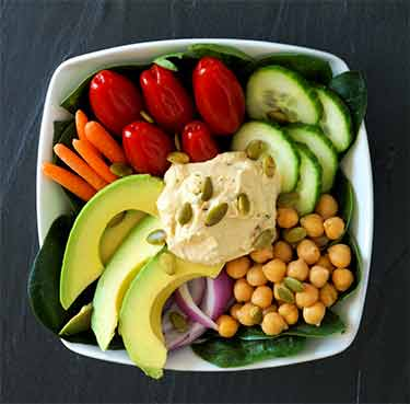 spinach salad with avocado, chickpea, tomato, cucumber, carrots