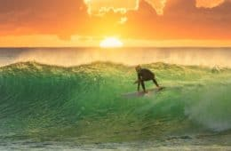 man surfing with sunrise in background