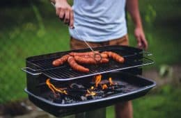 man barbecuing hot dogs