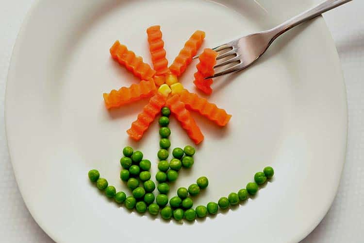 playing with peas and carrots on dinner plate