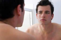 man looking in mirror at receding hairline