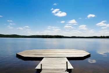 dock on calm lake with sunny blue sky