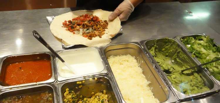 Chipotle employee making chicken burrito