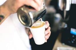 barista making coffee with white cream