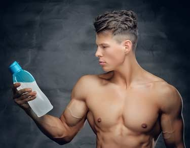 young buff bodybuilder holding protein drink