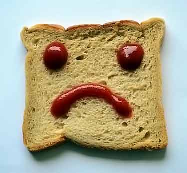 bread slice with sad face drawn in ketchup
