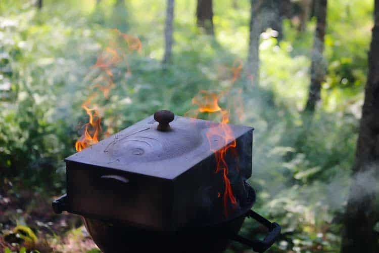 wood and charcoal smoking of fish in a cast iron smoker