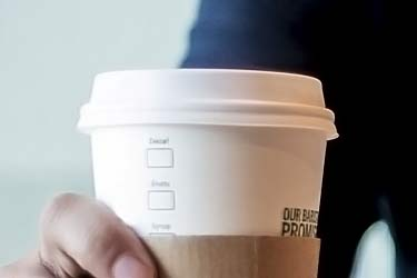man holding paper cup of coffee with plastic lid