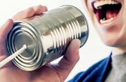 man yelling into tin can phone