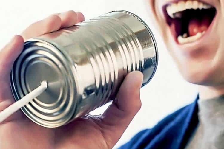 man yelling into tin can phone
