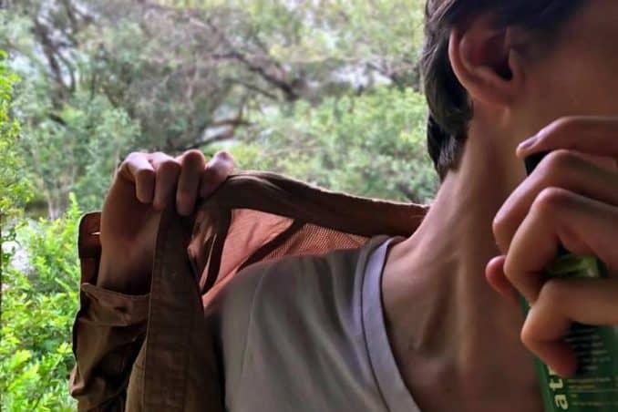 spraying repellent on neck