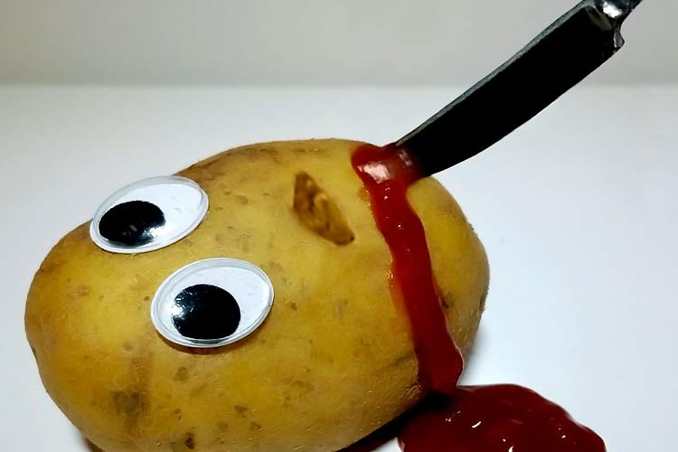raw potato with knife in it and blood ketchup