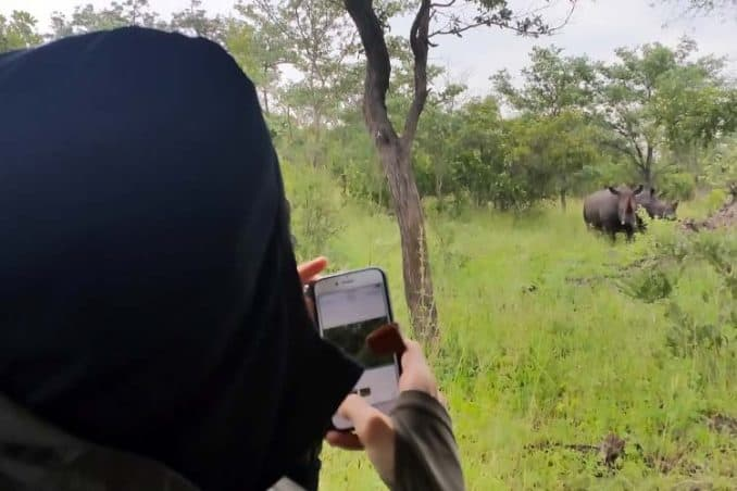 man next to wild rhino