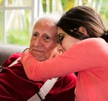 old man with Alzheimer's being hugged by granddaughter