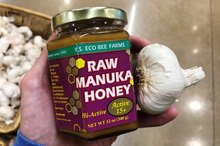 jar of organic Manuka honey with fresh whole garlic cloves