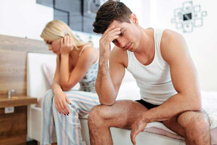 young couple in bed with man embarrassed by erectile dysfunction