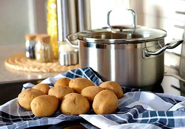 uncooked potatoes next to big pot on kitchen countertop