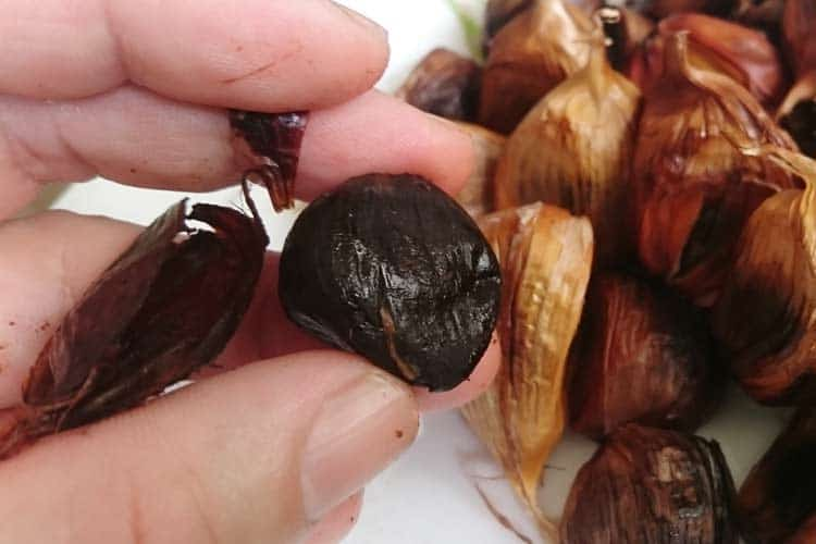 holding a raw black garlic clove