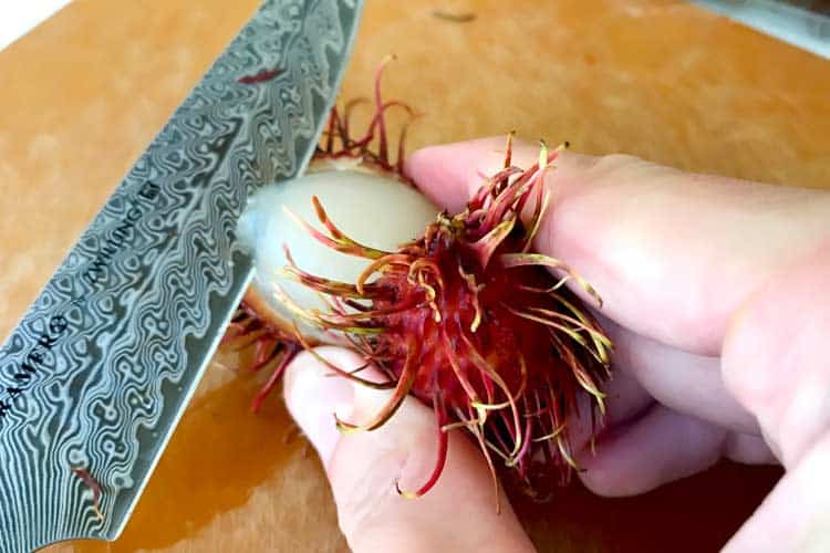 squeezing the peel off of a rambutan