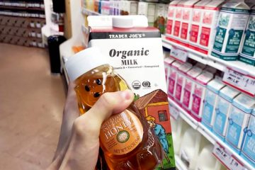 holding carton of organic milk and bottle of honey