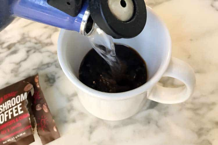 pouring hot water into coffee with mushroom powder