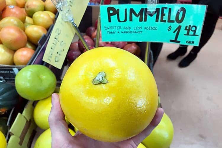 holding yellow pummelo at Trader Joe's