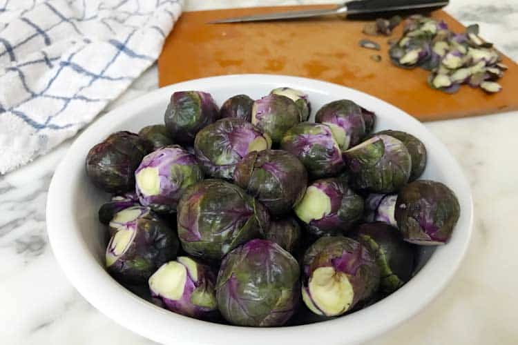 bowl of raw purple Brussels ready to bake, boil, fry, grill or roast