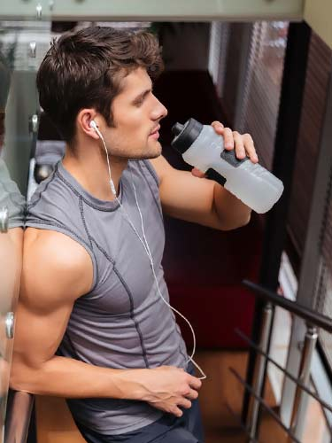attractive athletic man resting from exercise and drinking water bottle