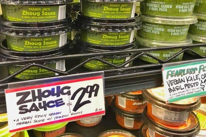 Trader Joe's zhoug sauce next to vegan pesto on shelf