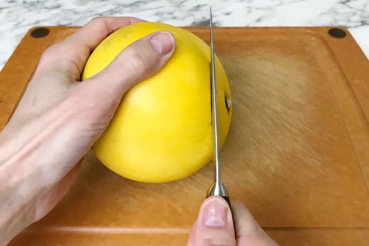 cutting top off a pomelo