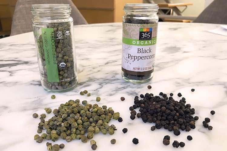 whole green and black peppercorns spread on table