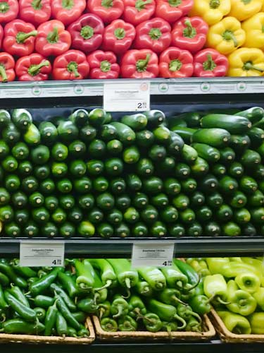 supermarket produce shelves of fresh colored bell peppers, cucumbers, and hot chili peppers