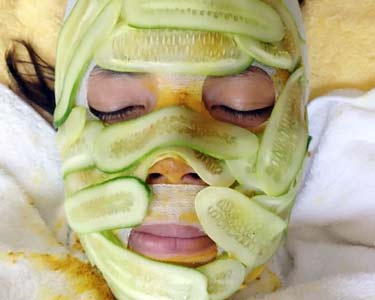 female face covered with cucumber slices during spa facial