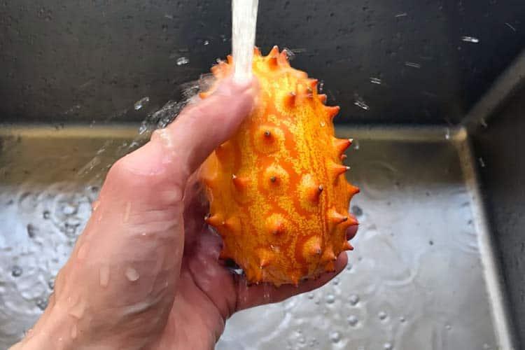 washing fresh horned melon in sink