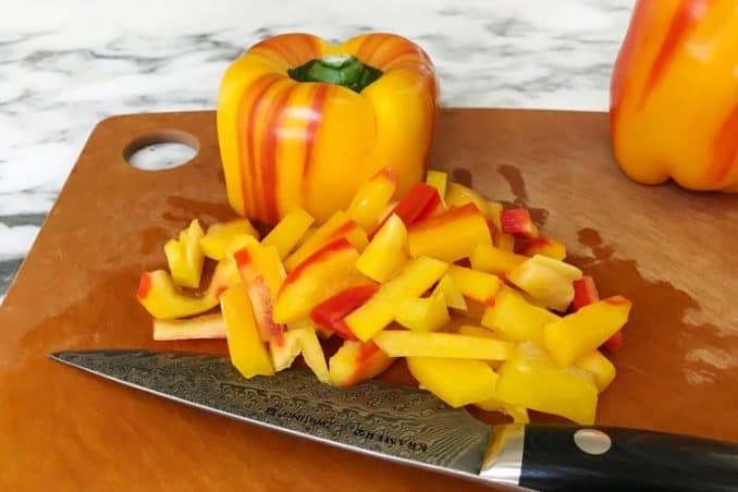 fresh striped pepper diced on cutting board