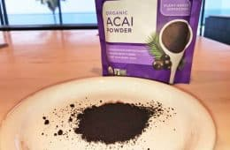 Navitas Organics freeze-dried acai powder on plate next to 8 oz bag